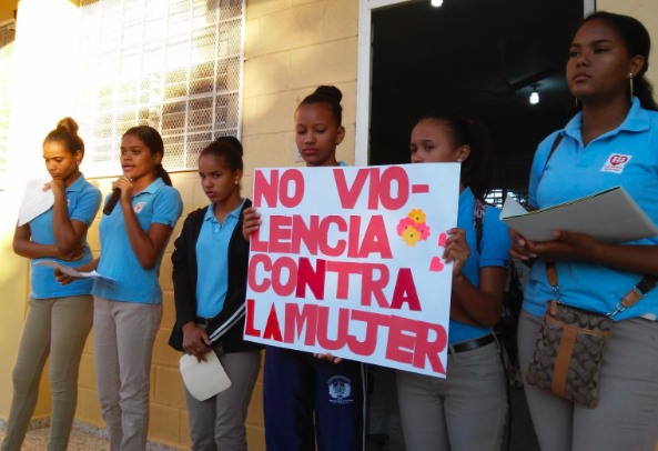 "Pictured: young women advocates from the school holding a sign that translates to ""Non-violence against women"""
